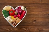 Heart health concept with related foods in white heart shaped bowl. potato  red peppers, broccoli, radish, red onion, garlic, dry beans, almonds, nuts, and other pulses were arranged in heart space plate on white background.
