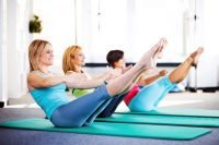 Women doing Pilates exercises on a exercising mat.