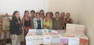 Annamaria Varriale, al centro, e Nadia Severino, all'estrema sinistra, insieme alle maestre e a un gruppo di allieve della scuola di ricamatrici