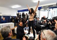 A femen militant performs a protest against Italian former prime minister and leader of 'Forza Italia' party Silvio Berlusconi during a general elections at a polling station in Milan, Italy, 4 March 2018.ANSA/DANIEL DAL ZENNARO