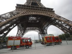 Rescue workers vehicles park just down the Eiffel Tower Monday, May 20, 2019 in Paris. The Eiffel Tower has been closed to visitors after a person has tried to scale it. (ANSA/AP Photo/Michel Euler) [CopyrightNotice: Copyright 2019 The Associated Press. All rights reserved.]