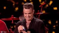 robbie_williams_caught_applying_hand_sanitiser_after_singing_auld_lang_syne__daily_mail_online_640_ori_crop_master__0x0_640x360