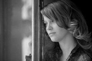 Junge blonde Frau steht traurig am Fenster und schaut hinaus.