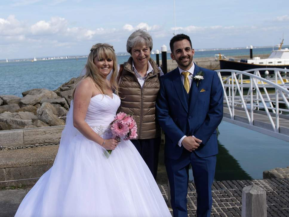 Theresa May «braccata» da una coppia di sposini, lei si ferma per una foto: «Ma non ho il vestito adatto...»